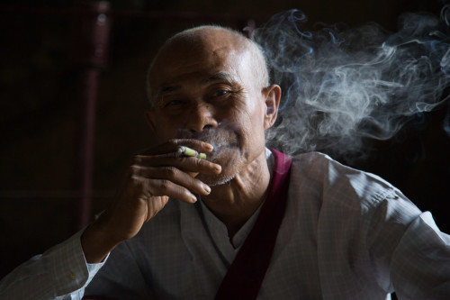A man smokes in a cave temple